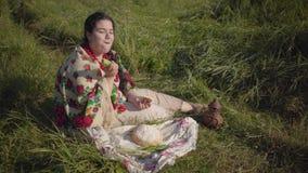 Mooie te zware vrouwenzitting in gras op het gebied die het brood van verse brood en komkommer eten tradities stock footage