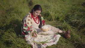 Mooie te zware vrouwenzitting in gras op het gebied die een stuk van vers brood eten Tradities, gezond voedsel stock video