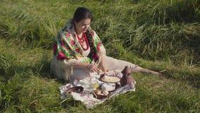 Mooie te zware vrouwenzitting in het gras die pannekoeken met kwark en honing voorbereidingen treffen te eten Gezond stock videobeelden