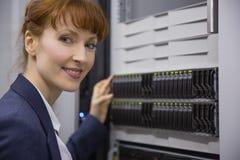 Mooie technicus die bij camera naast servertoren glimlachen royalty-vrije stock afbeelding