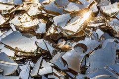 Mooie textuur van het gebroken gekleurde glas in kleine scherpe stukken met water op de oranje zonsondergang met blauwe hemel en  stock afbeeldingen