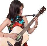 Mooie tiener die een akoestische guita speelt die op wit wordt geïsoleerd royalty-vrije stock afbeeldingen
