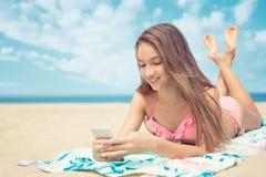 Mooie tiener die een slimme telefoon met behulp van die op het strand met het overzees en horizon in de achtergrond liggen stock fotografie