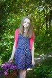 Mooie tiener die in hout met een mand van bloemen lopen Royalty-vrije Stock Afbeelding