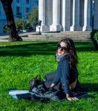 Mooie tiener die met donkere haar en zonglazen in een openbare tuin zitten stock foto