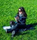 Mooie tiener die met donkere haar en zonglazen op haar telefoon schrijven royalty-vrije stock afbeeldingen
