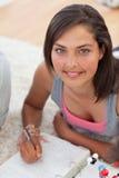 Mooie tiener die op de vloer bestudeert Stock Afbeeldingen