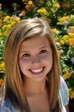 Mooie tiener grote glimlach naast bloemtuin Royalty-vrije Stock Afbeeldingen