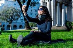 Mooie tiener met donkere haar en zonglazen die selfies nemen royalty-vrije stock afbeeldingen