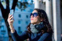 Mooie tiener met donkere haar en zonglazen die selfies nemen - sluit schot stock foto's