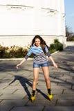 Mooie tiener met gele rolschaatsen royalty-vrije stock foto's
