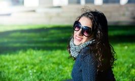 Mooie tiener met het donkere haar en zonglazen glimlachen stock foto's