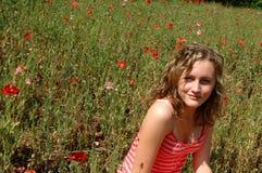 Mooie tiener op bloemgebied Stock Afbeelding