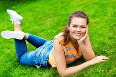 Mooie tiener op groen gras Stock Afbeeldingen