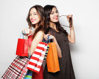 Mooie tienermeisjes die het winkelen zakken, over witte backgro dragen stock fotografie