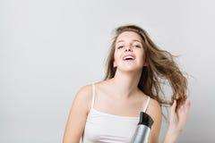 Mooie tienerslag die haar haar drogen en camera bekijken Stock Afbeelding