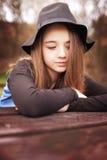 Mooie tienerzitting openlucht bij een picknicklijst Royalty-vrije Stock Afbeelding