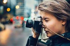Mooie toeristenvrouw die foto met uitstekende oude camera in de stad nemen stock afbeelding