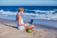 Mooie toevallige vrouw met laptop op het strand met overzees i stock afbeelding