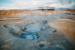 mooie toneelmening van de geothermische hete lentes met stoom en houten brug stock afbeeldingen