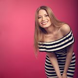 Mooie toothy glimlachende positie blonde vrouw in gestreepte kleding po stock foto's