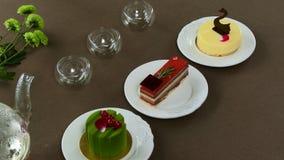 Mooie transparante theepotketel met smakelijke groene zwarte thee met appel, met kaarsen en met dessert in stock fotografie