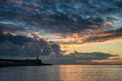 Mooie trillende zonsopganghemel over kalme wateroceaan met lightho Royalty-vrije Stock Afbeeldingen