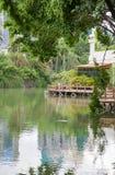 Mooie tuin met brug en bezinning in het meer stock foto's