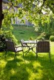 Mooie tuin met witte lijst en stoel Stock Afbeeldingen