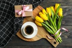 Mooie tulpen, kop van koffie, heden en handdoek stock foto