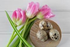 Mooie tulpen met kwartelseieren op lichte houten achtergrond De lente en Pasen-vakantieconcept Stock Fotografie