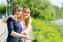 Mooie tweelingenmeisjes die pret hebben die weg eruit zien Royalty-vrije Stock Foto