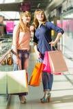 Mooie tweelingenmeisjes die pret met het winkelen in winkelcomplex hebben Royalty-vrije Stock Foto's