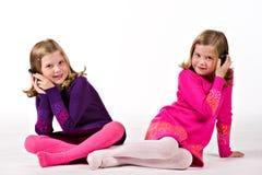 Mooie tweelingmeisjes op celtelefoons stock fotografie