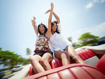 Mooie tweelingzusters die pret in cabriolet auto hebben Stock Afbeeldingen