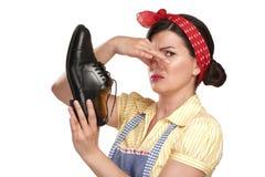 Mooie uitstekende huishoudster die stinkende schoenen houden Stock Afbeeldingen