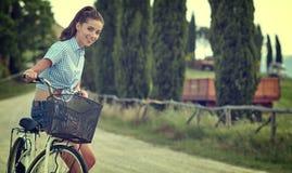 Mooie uitstekende meisjeszitting naast fiets, de zomertijd stock foto