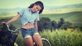 Mooie uitstekende meisjeszitting naast fiets, de zomertijd royalty-vrije stock foto's