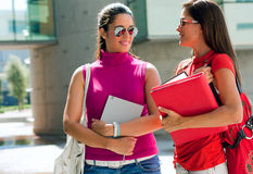 Mooie universiteitsvrienden die op campus spreken Stock Foto's