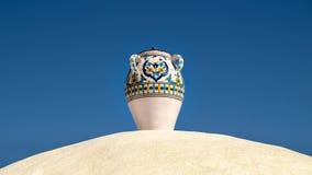 Mooie vaas die zich op de witte muur voor de blauwe hemel bevinden Royalty-vrije Stock Foto's