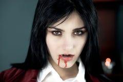 Mooie vampier die met bloed camera kijken stock foto's
