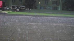 Mooie verbazende lage hoek die langzame motiemening over de daling van regendalingen kalm op de grijze natte betonweg van het bes stock videobeelden