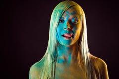 Mooie verleidelijke vrouw die in blauwe kleuren Holi lippen likken Stock Fotografie