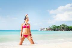 Mooie, verleidelijke vrouw in het fascineren het swimwear stellen op knieën op de zeekust in Thailand stock afbeelding