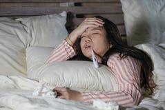 Mooie vermoeide en zieke Aziatische Chinese vrouw die op bed thuis zieken liggen die aan koude griep en hoofdpijn lijden die onwe royalty-vrije stock foto's