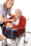 Mooie verpleegster die bejaarde patiënt behandelt Royalty-vrije Stock Foto's