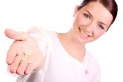 Mooie verpleegster die twee pillen aanbiedt Stock Afbeeldingen