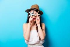 Mooie verraste jonge vrouw die met zeesterren zich in fron bevinden Royalty-vrije Stock Foto