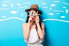 Mooie verraste jonge vrouw die met zeesterren zich in fron bevinden Stock Foto's