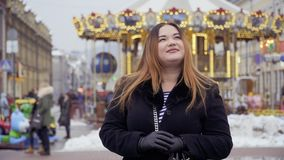 Mooie vette vrouwentribunes tegen carrouselachtergrond stock videobeelden